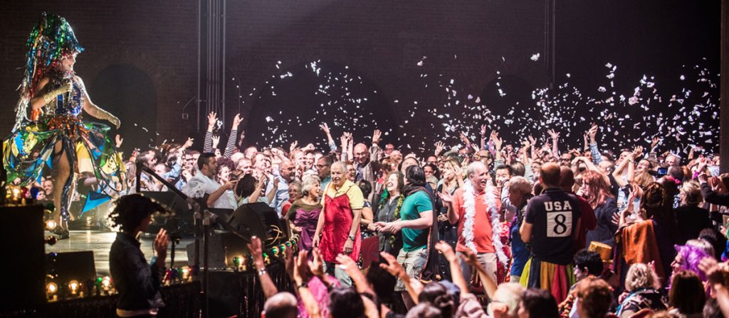 Crowd throwing confetti while Taylor Mac is performing on stage.