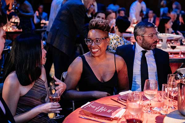Black woman Gala attendee smiling while in conversation at the Gala dinner table.